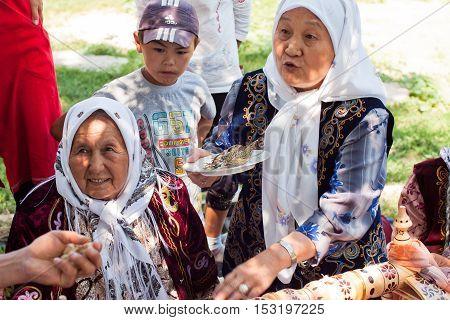 KEMIN, KYRGYZSTAN - AUGUST 2, 2013: Elderly village woman tells the story of folk traditions and burn incense on August 2, 2013 in Kyrgyzstan. Central Asian Kyrgyzstan has population near 5.4 million