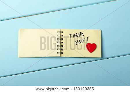 Thank You A spiral Notepad that has the words Thank You wooden red heart over a distressed wood turquoise background. Valentine's Day