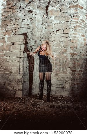 woman in leather with chains in old castle. Helloween theme