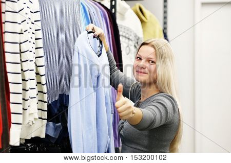 Happy woman in clothing store showing thumbs up. Girl in clothes shop