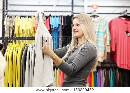 Smile woman in clothing shop. Girl in clothes shop