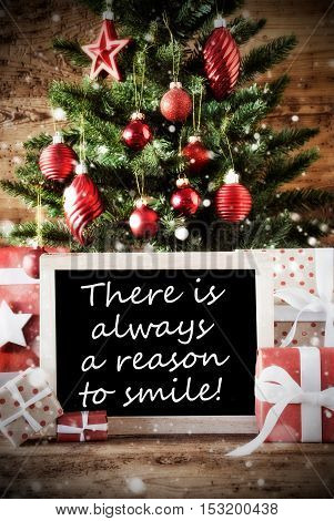 Christmas Card For Seasons Greetings. Christmas Tree With Balls. Gifts Or Presents In The Front Of Wooden Background. Chalkboard With English Quote There Is Always A Reason To Smile