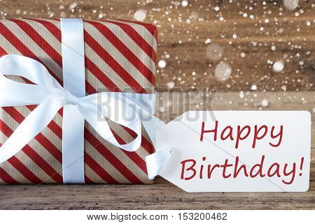 Christmas Gift Or Present On Wooden Background With Snowflakes. Card For Seasons Greetings. White Ribbon With Bow. English Text Happy Birthday