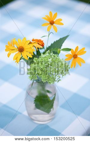 Closeup picture of beautiful vase with yellow flowers in outdoors. Bouquet of wildflowers on rustic table at country cottage.