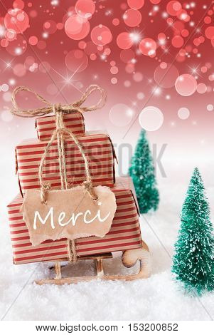 Vertical Image Of Sleigh Or Sled With Christmas Gifts Or Presents. Snowy Scenery With Snow And Trees. Red Sparkling Background With Bokeh. Label With French Text Merci Means Thank You