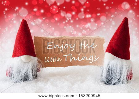 Christmas Greeting Card With Two Red Gnomes. Sparkling Bokeh And Christmassy Background With Snow. English Quote Enjoy The Little Things