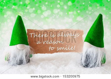 Christmas Greeting Card With Two Green Gnomes. Sparkling Bokeh And Natural Background With Snow. English Quote Always Reasons To Smile