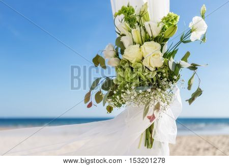 Bunch of flowers in a vase for a wedding ceremony. On the background of the sea.