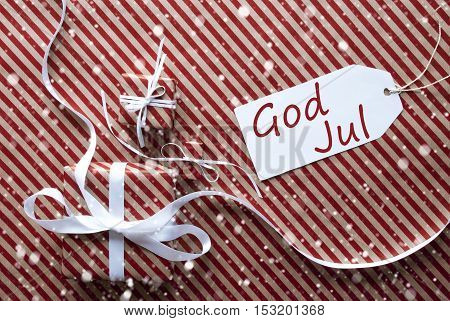 Two Gifts Or Presents With White Ribbon. Red And Brown Striped Wrapping Paper. Christmas Or Greeting Card With Snowflakes. Label With Swedish Text God Jul Means Merry Christmas