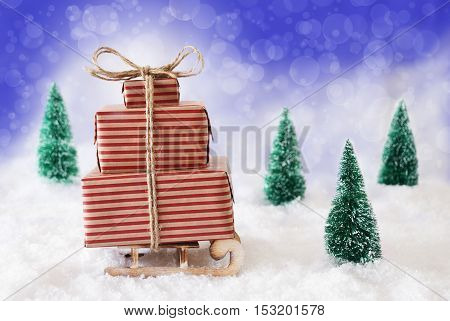 Sleigh Or Sled With Christmas Gifts Or Presents. Snowy Scenery With Snow And Trees. Blue Background With Bokeh Effect.