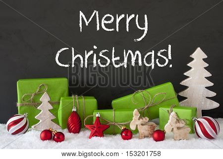 English Text Merry Christmas. Green Gifts Or Presents With Christmas Decoration Like Tree, Moose Or Red Christmas Tree Ball. Black Cement Wall As Background With Snow.