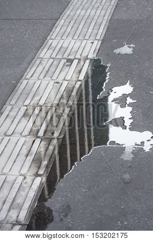 Sidewalk with water puddle on cement surface