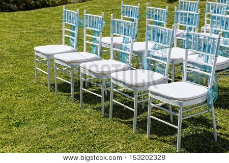 Rows of chairs for guests at a wedding ceremony. In the garden.