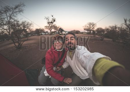 Adult caucasian couple taking selfie in camping site at dusk. Adventure in National Park South Africa. Toned image.