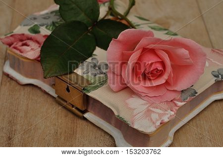 A closed notebook with a pink flower