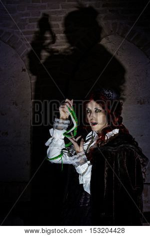 devil vampire woman with snake in medieval costume on Halloween