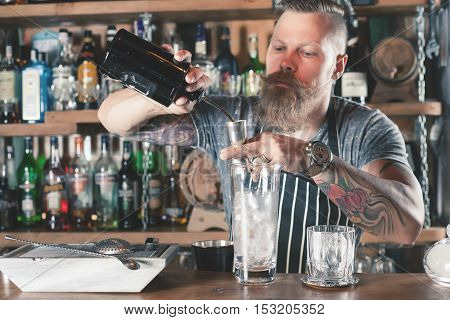 Handsome barman is making cocktail Chocolate Negroni at night club. Bartender has a mustache and stylish hairstyle. Old fashioned cocktail. Alcohol