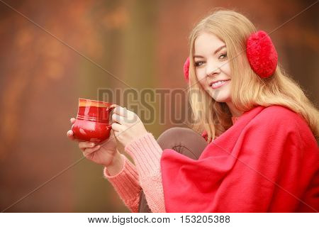 Nature outdoor relax cozy concept. Girl with cup in park. Young blonde lady sitting on bench covered by blanket holding hot glass drinking beverage.
