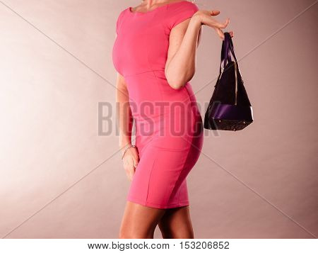 Love to shopping. Satisfaction from buying new fashionable accessories and clothes. Elegant woman with purchase. Female in pink with deep blue bag.