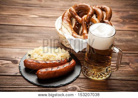 Pretzels, bratwurst and sauerkraut on wooden table