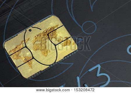 World map made of gold on a chip of the old black credit card closeup top view.