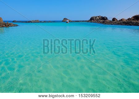 View on the lagoon with crystal emerald sea water a boat and volcanic cliffs on the Canary island Lobos Fuerteventura Spain.