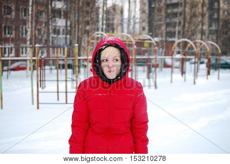 A young girl in a red jacket stands in the yard at the children's square during a snowfall she froze
