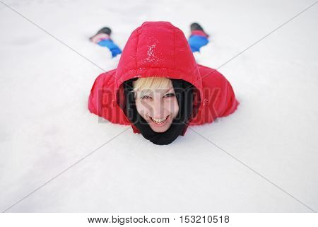 Portrait of happy smiling girl in a red hooded jacket in snowdrift on a Sunny winter day.