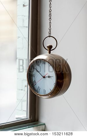 original clock with metal case hanging on  chain in plain interior
