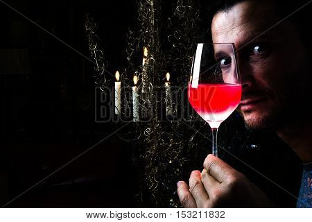 Portrait of a man with a glass of red wine in front of his face with lights reflections on the glass and eyes