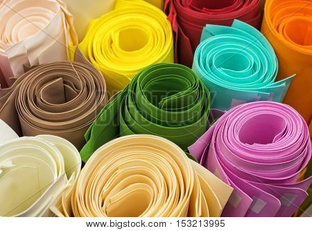 Rolls of colored paper - green brown blue pink orange red white. Soft focus
