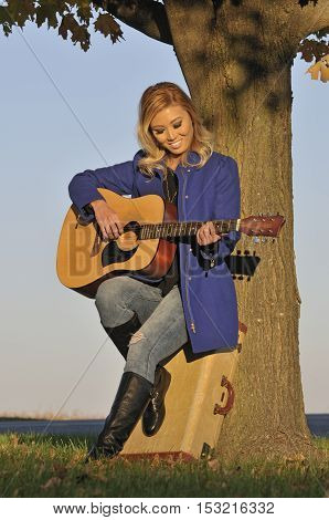 Beautiful asian woman playing guitar outside in the fall
