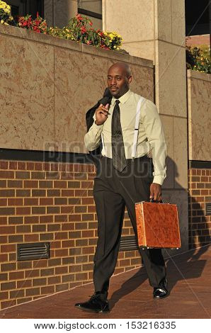 Well-dressed African American businessman walking with suitcase near office building in the city