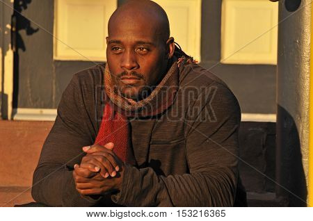 African American man wearing a scaft on Autumn evening warming up hands