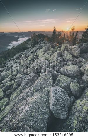 View of the stony hills glowing by evening sunlight. Dramatic autumn scene. Yavirnuk ridge, Carpathians, Ukraine, Europe. Toned like Instagram filter
