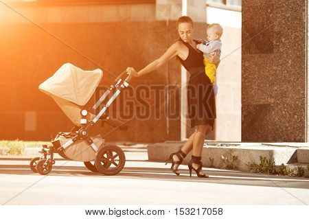 Trendy modern mother on a city street with a pram. Young mother walks with a child in 