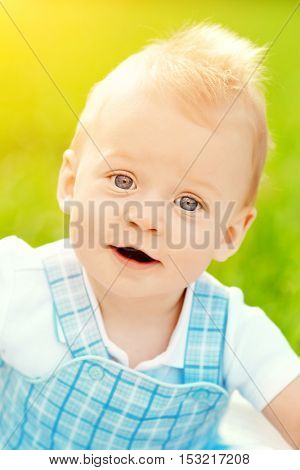 Cute little baby in summer  park on the grass. Sweet toddler outdoors. Smiling emotional kid on a walk. Smile of a child