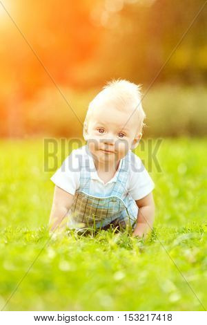Cute little baby in the park on the grass. Sweet baby outdoors. Smiling emotional kid on a walk. Smile of a child