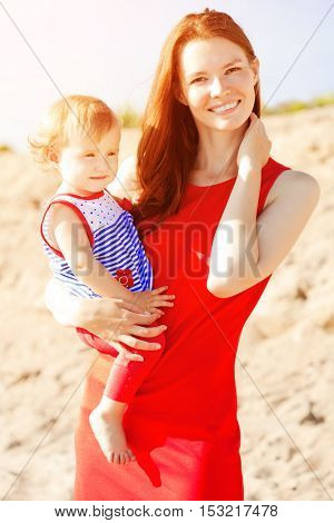 Beauty Mom and baby outdoors. Happy family playing on the beach. Mom and baby. Mother 