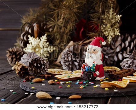 Cards Christmas figurine Santa Claus Christmas THE BACKGROUND branches, cones, on a wooden table, selective focus