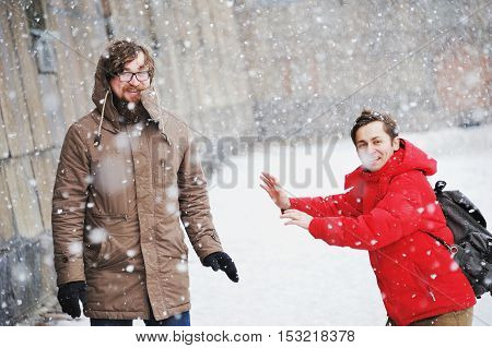 Two young men met on a city street during a snowfall and happily laughing