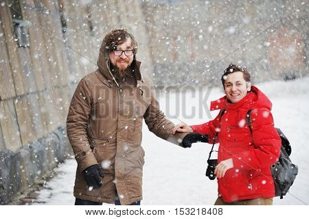 Two young men met on a city street and happily laugh during a snowfall.