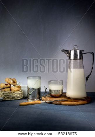 Milk from a jug pouring into glass on old wooden table. space for text