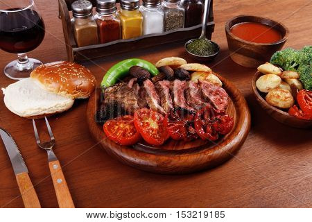 fresh roast bbq beef meat ribeye steak on wooden plate served with tomato juice in wooden cup, boiled broccoli, baked tomatoes and potatoes, with white bun, red wine glass on light walnut wooden table