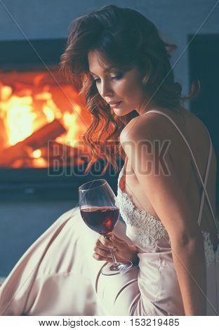 Woman with a glass of wine by the fireplace