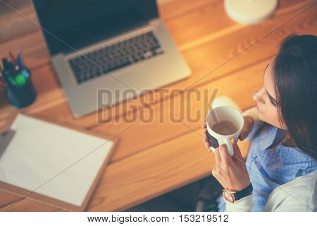 Portrait relaxed young woman sitting at her desk holding cup of coffee