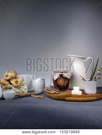 Still life with a jar of plum jam, fresh bread rolls on wooden table gray background.