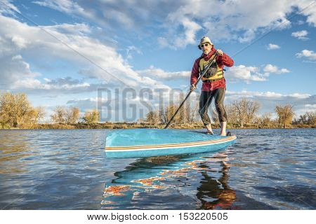 paddling stand up paddleboard on lake in Colorado, fall scenery