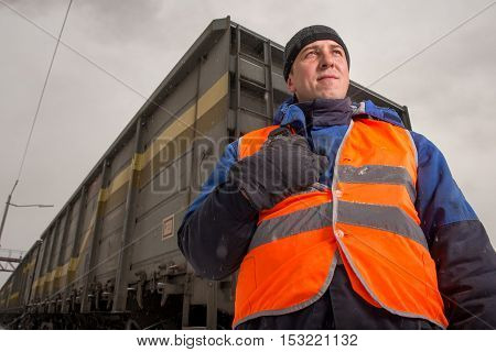 Russia - October, 2016: Rail worker coordinating cargo loading to transport train on the tracks
