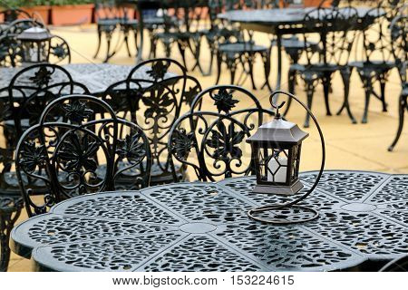 chairs and tables with old lantern, outdoor restaurant